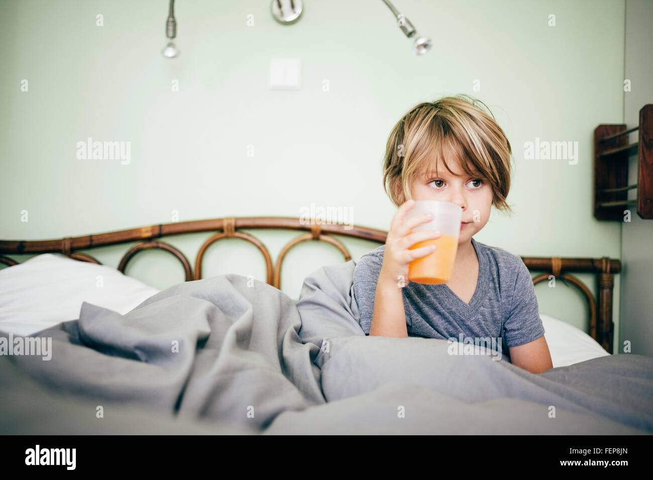 Boy sitting in bed drinking beaker of orange juice, looking away, Bludenz, Vorarlberg, Austria - Stock Image