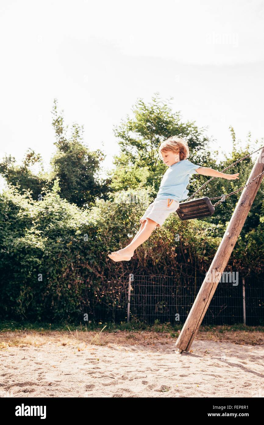 Side view of boy in mid air jumping from swing, Ulm, Baden Wuerttemberg, Germany - Stock Image