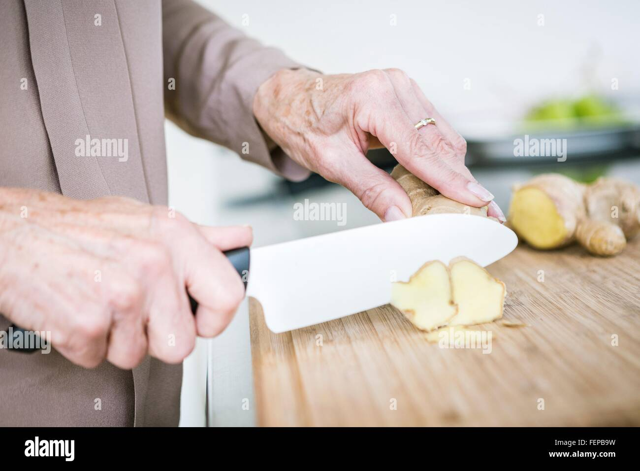 Close up of senior female hands chopping ginger - Stock Image