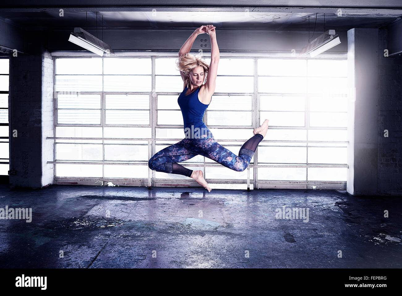 Female dancer leaping in front of warehouse window - Stock Image