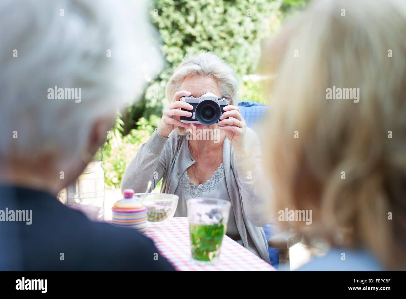 Senior woman, taking photograph of friends in garden - Stock Image