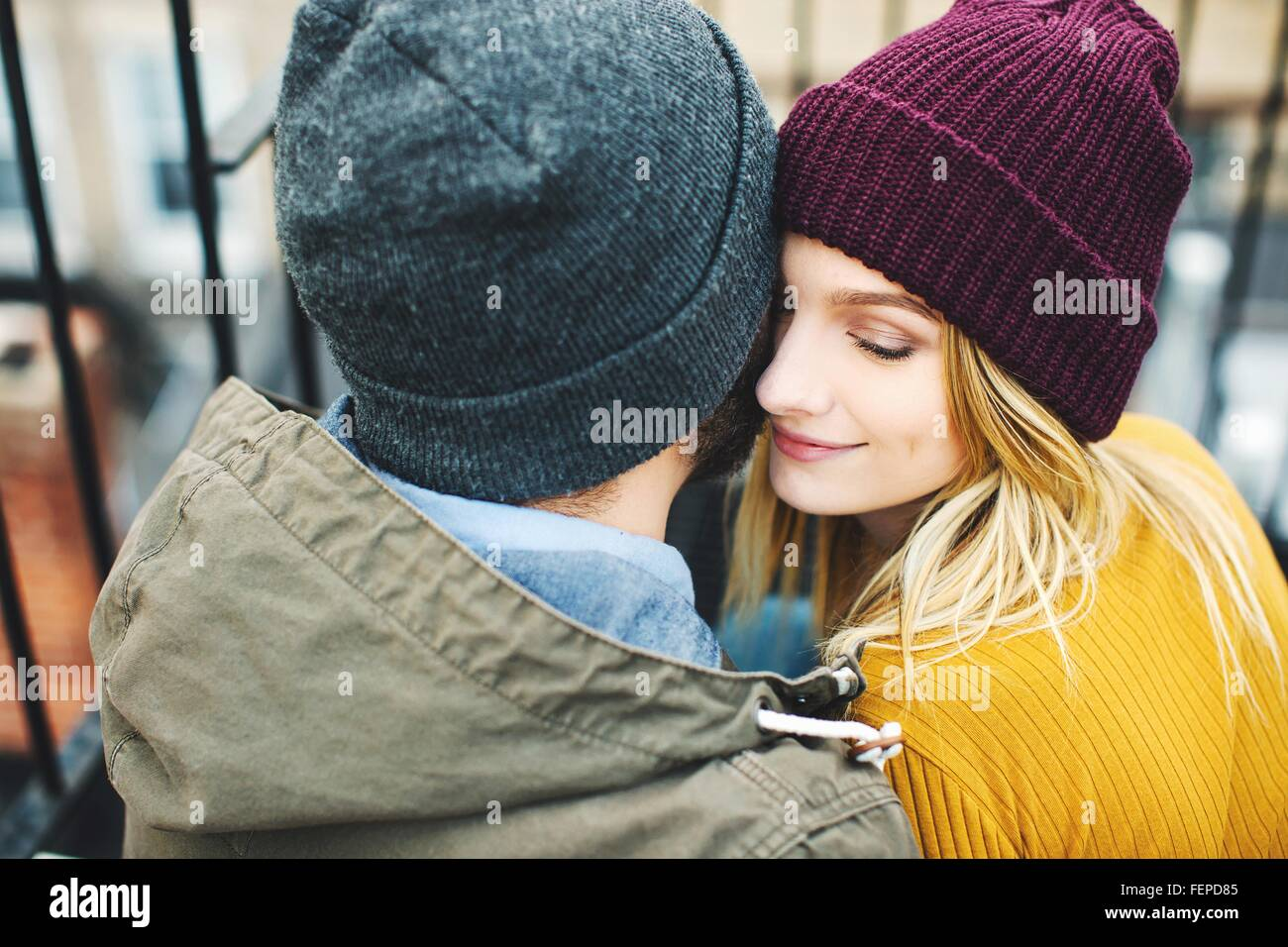 Romantic young couple wearing knitted hats sitting on stairway - Stock Image
