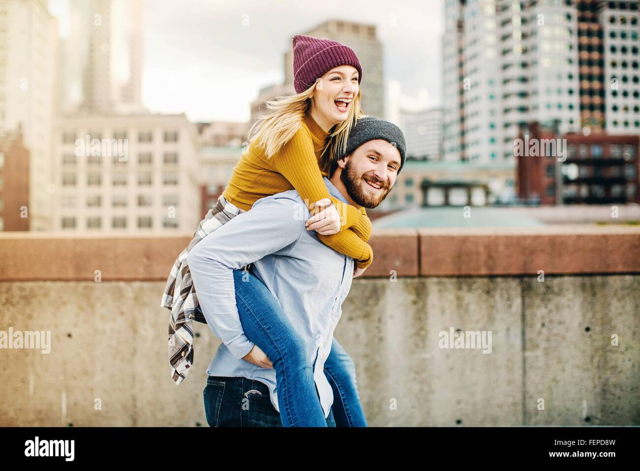 Young man giving girlfriend a piggyback on city rooftop terrace - Stock Image