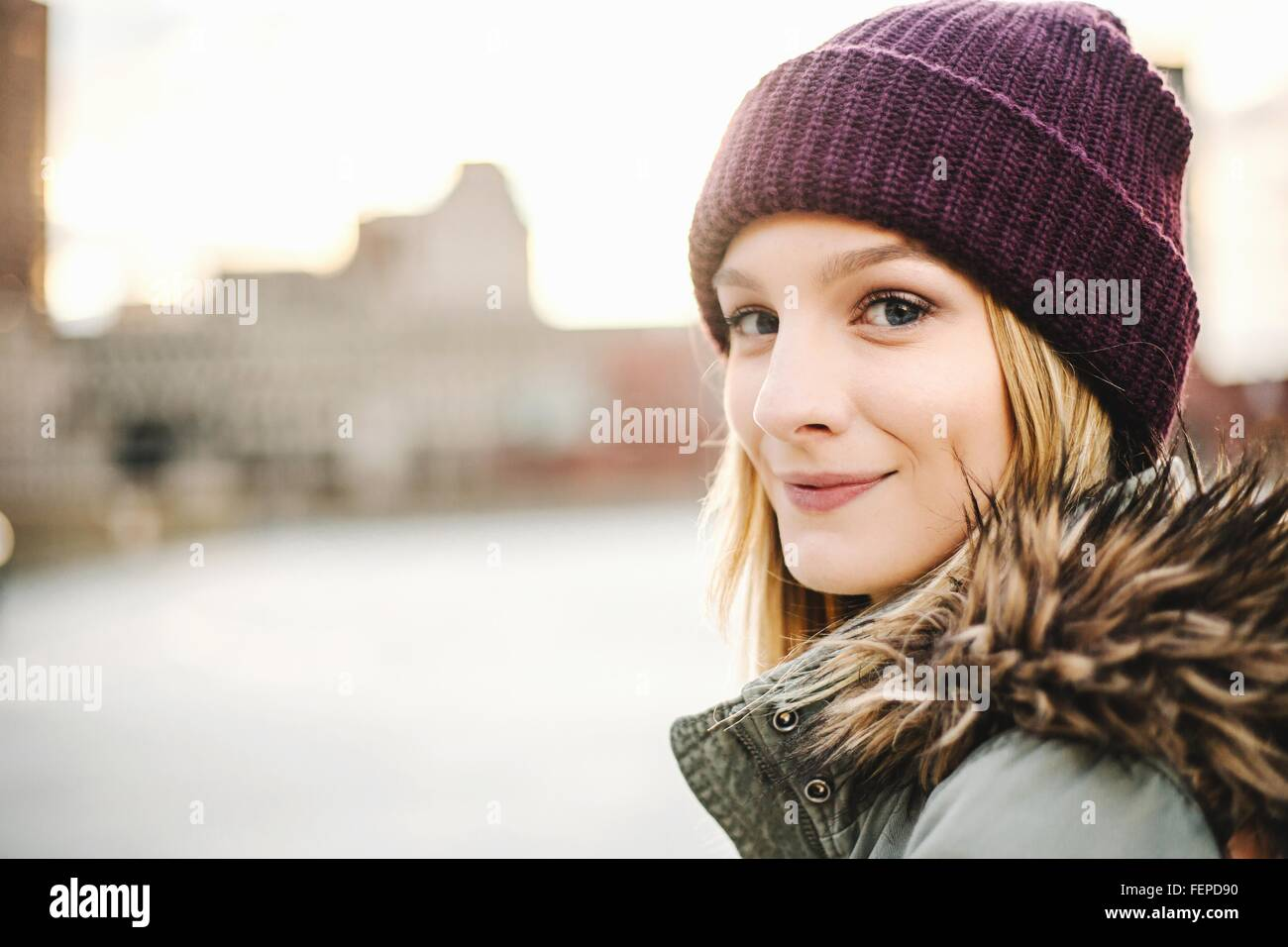 Portrait of young woman wearing knitted hat and fur hood - Stock Image
