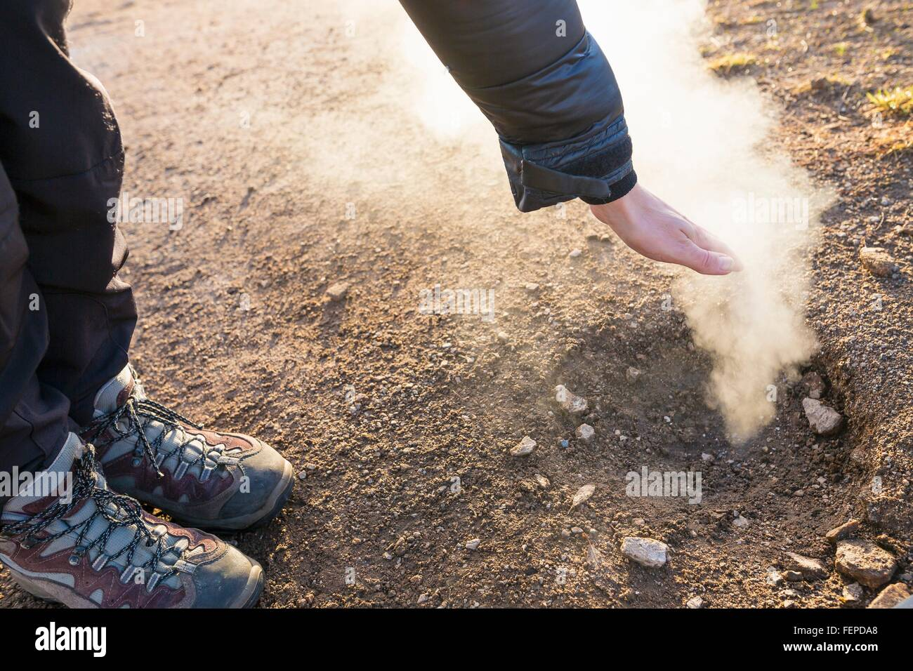 Woman, hand over small vent in the area of The Great Geysir, Haukadalur valley, South West Iceland - Stock Image