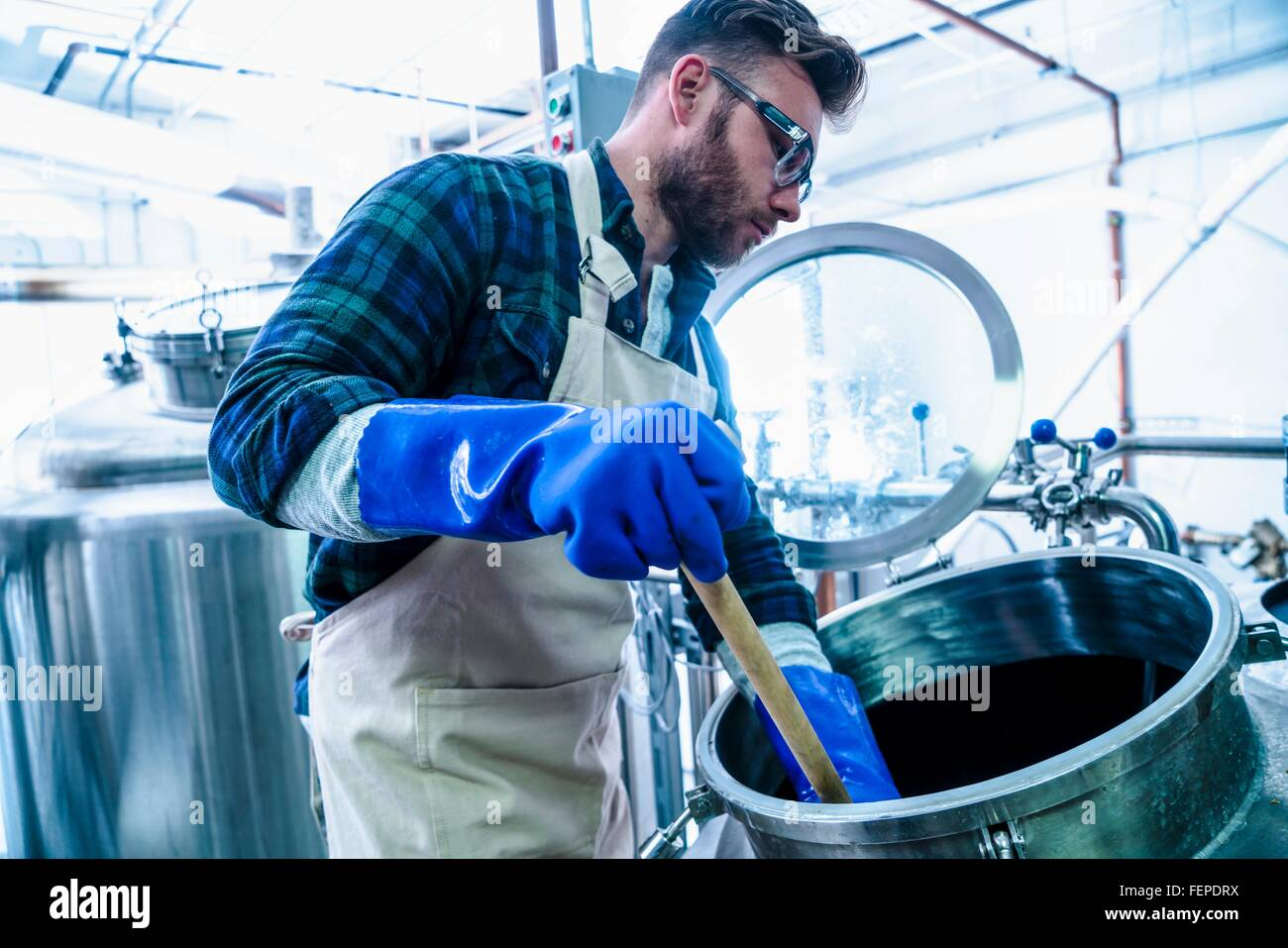 Side view of young man in brewery wearing apron and protective gloves testing beer in tank - Stock Image