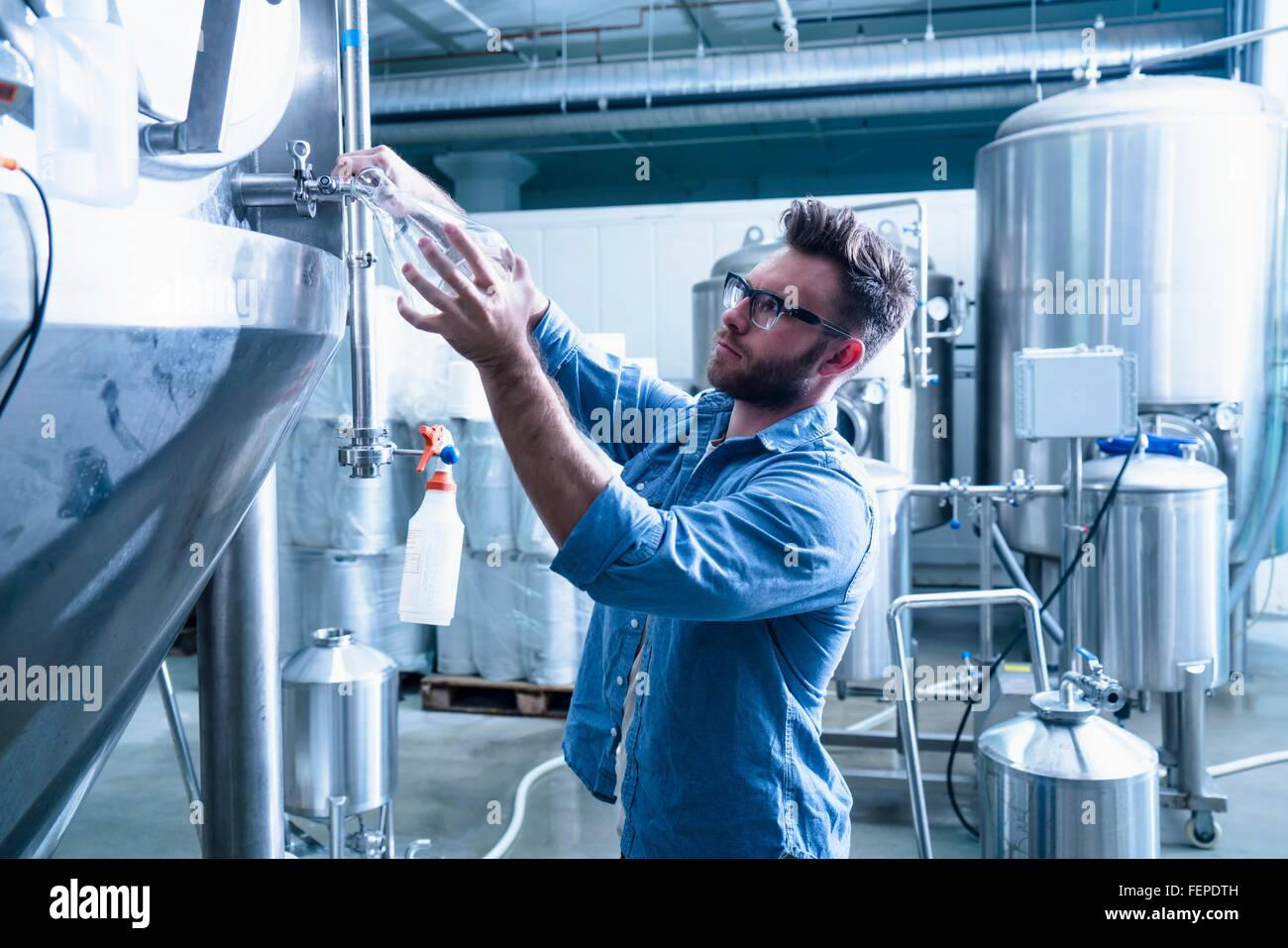 Young man in brewery filling flask with beer - Stock Image