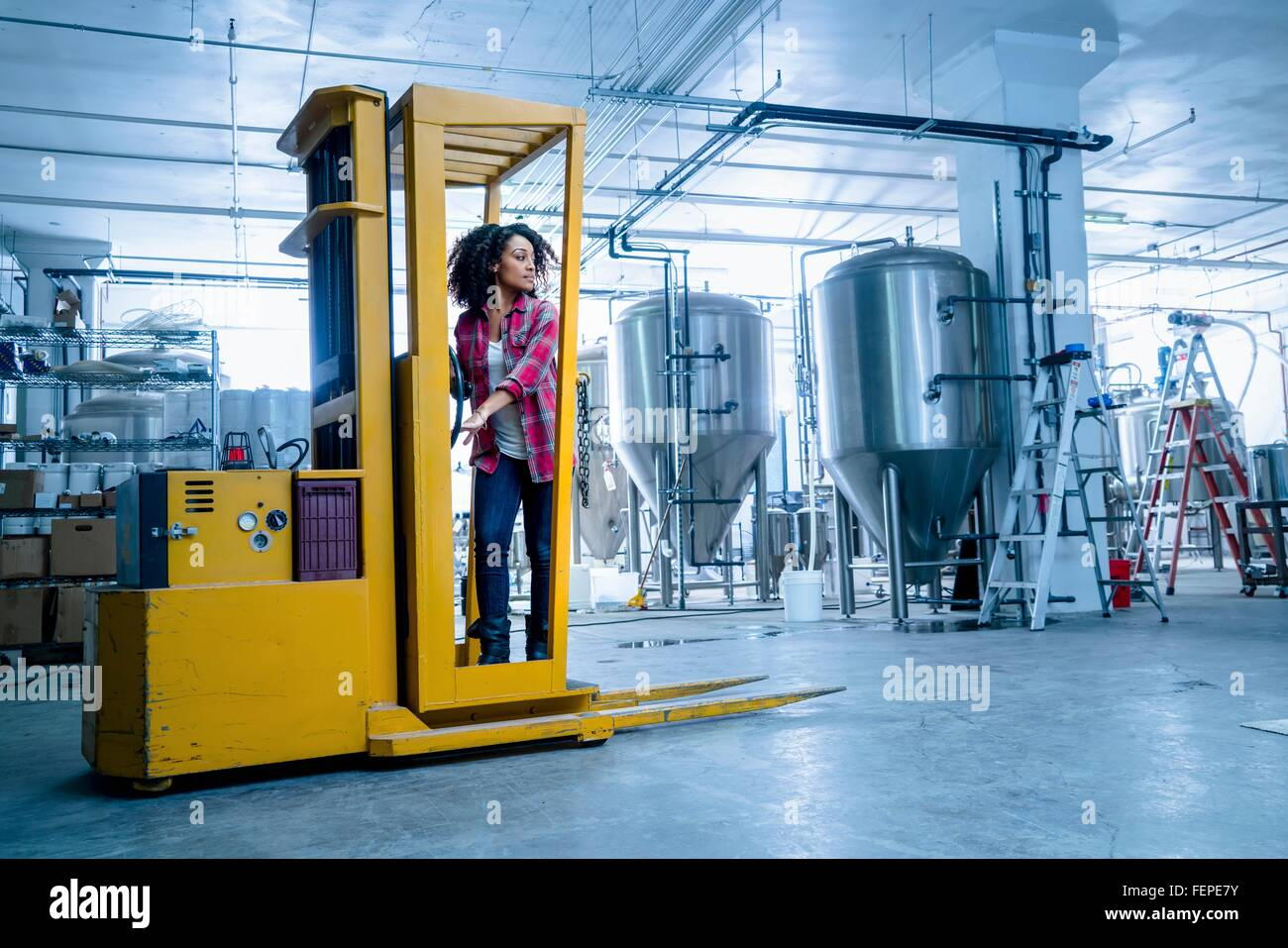 Mid adult woman in brewery driving forklift truck looking away - Stock Image