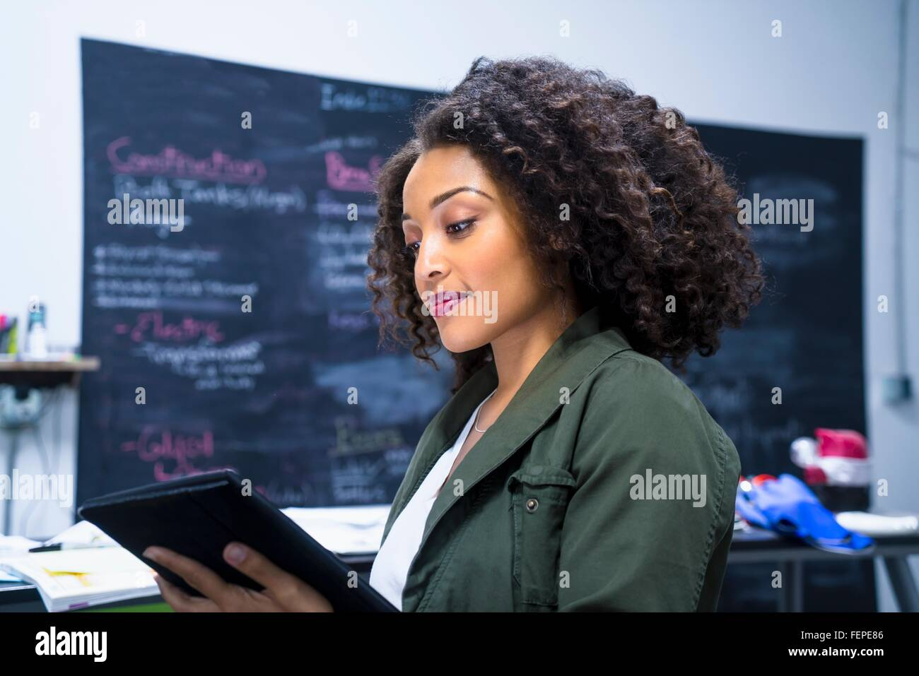 Side view of mid adult woman in workplace looking at digital tablet - Stock Image