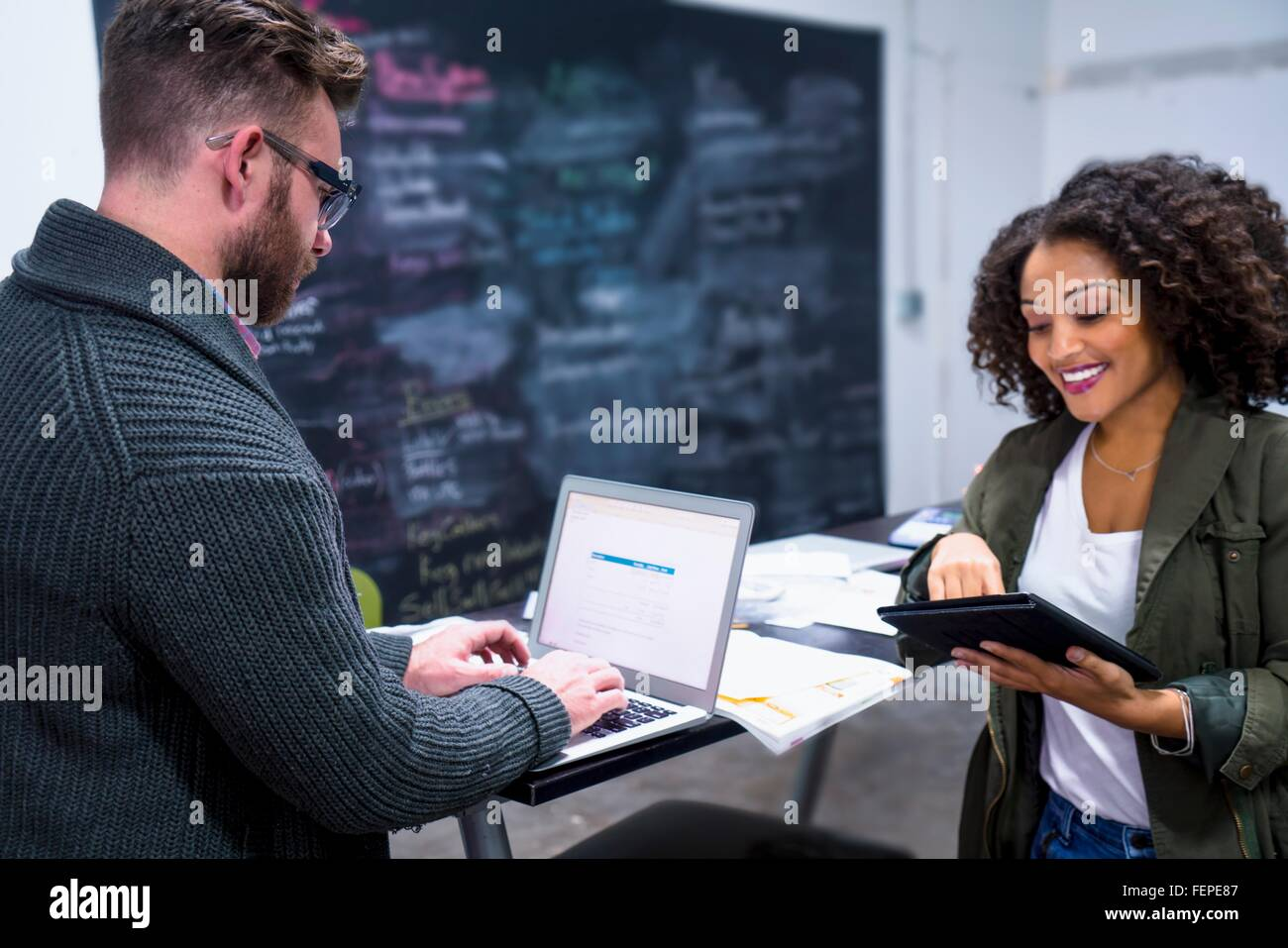 Colleagues in workplace using digital tablet and laptop smiling - Stock Image