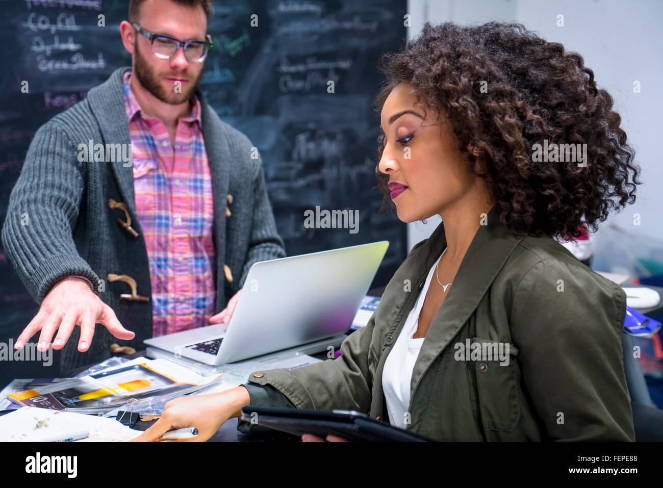 Colleagues in workplace using digital tablet and laptop - Stock Image
