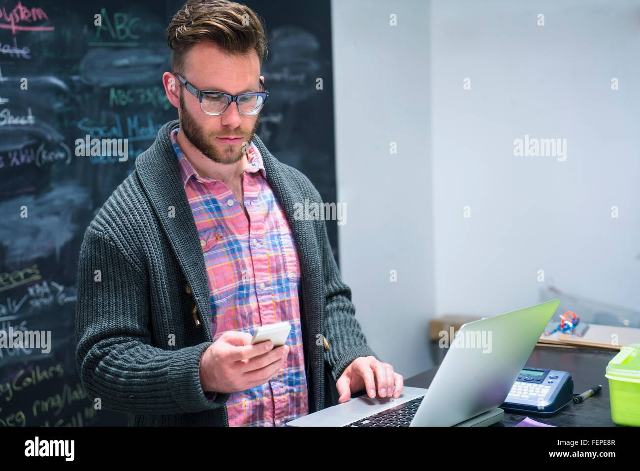 Young man in workplace using laptop looking at smartphone - Stock Image