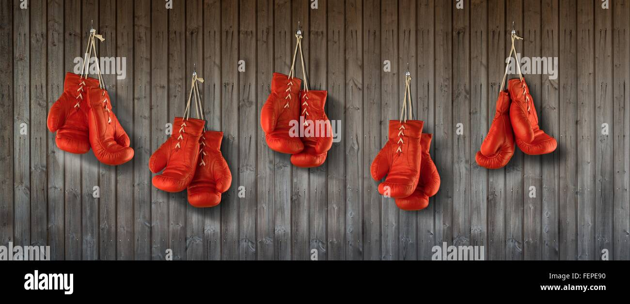 Row of red boxing gloves hanging from wood panelled wall - Stock Image