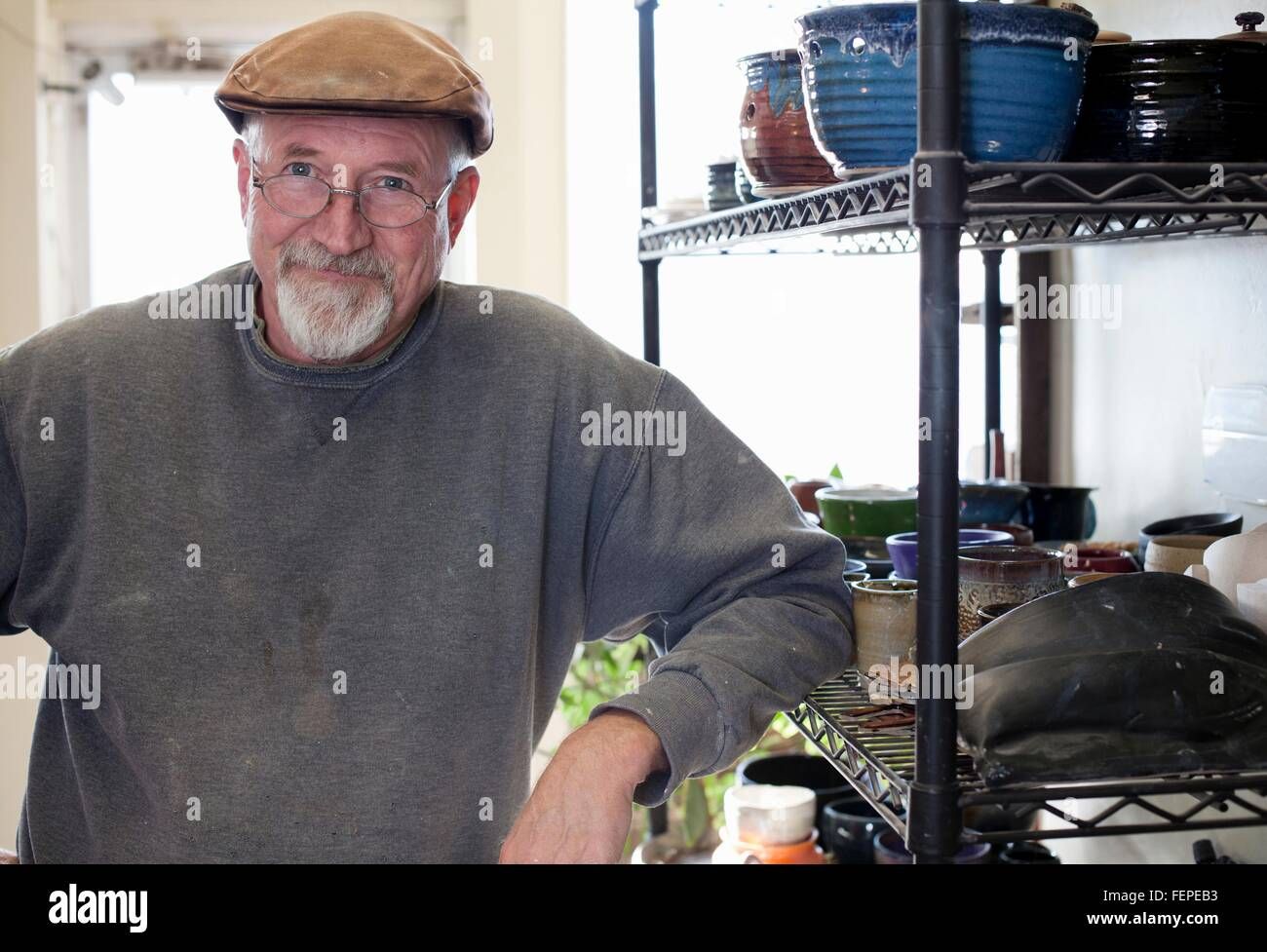 Potter wearing flat cap leaning against shelving display of glazed clay pots looking at camera smiling - Stock Image