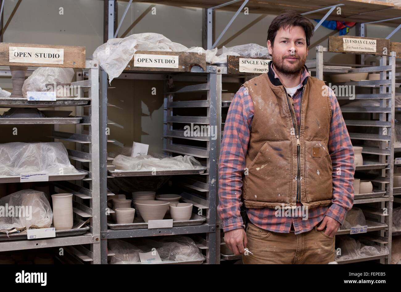 Potter in storage room, hand in pocket looking at camera smiling - Stock Image