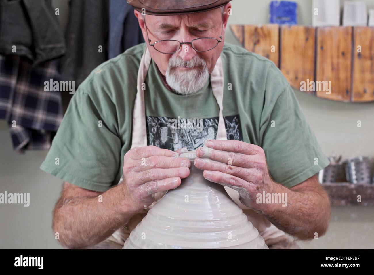 Potter wearing flat cap finishing shaping clay vase, looking down - Stock Image