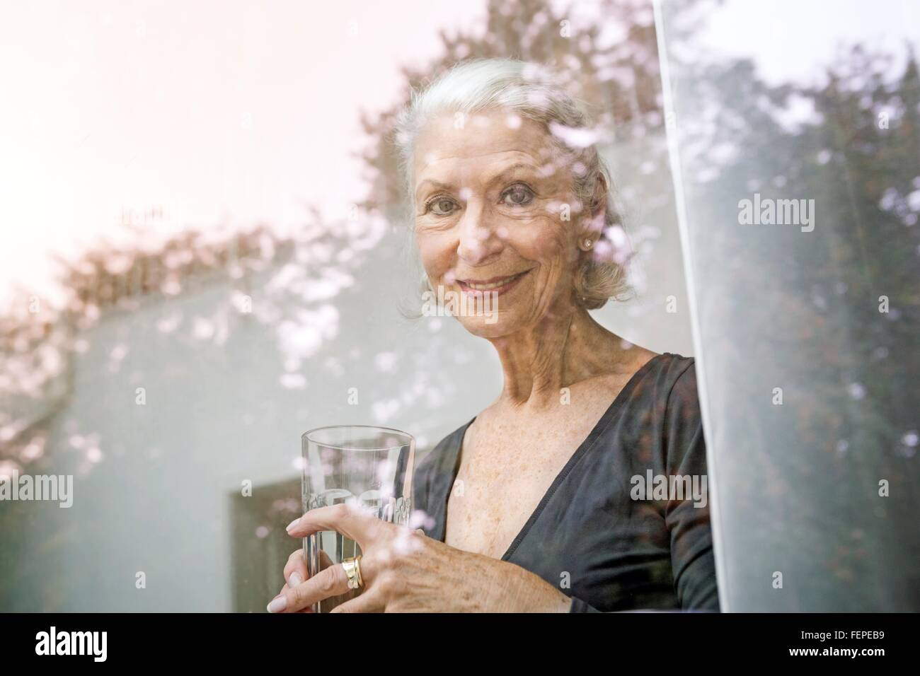 View through window of senior woman holding tumbler looking at camera smiling - Stock Image