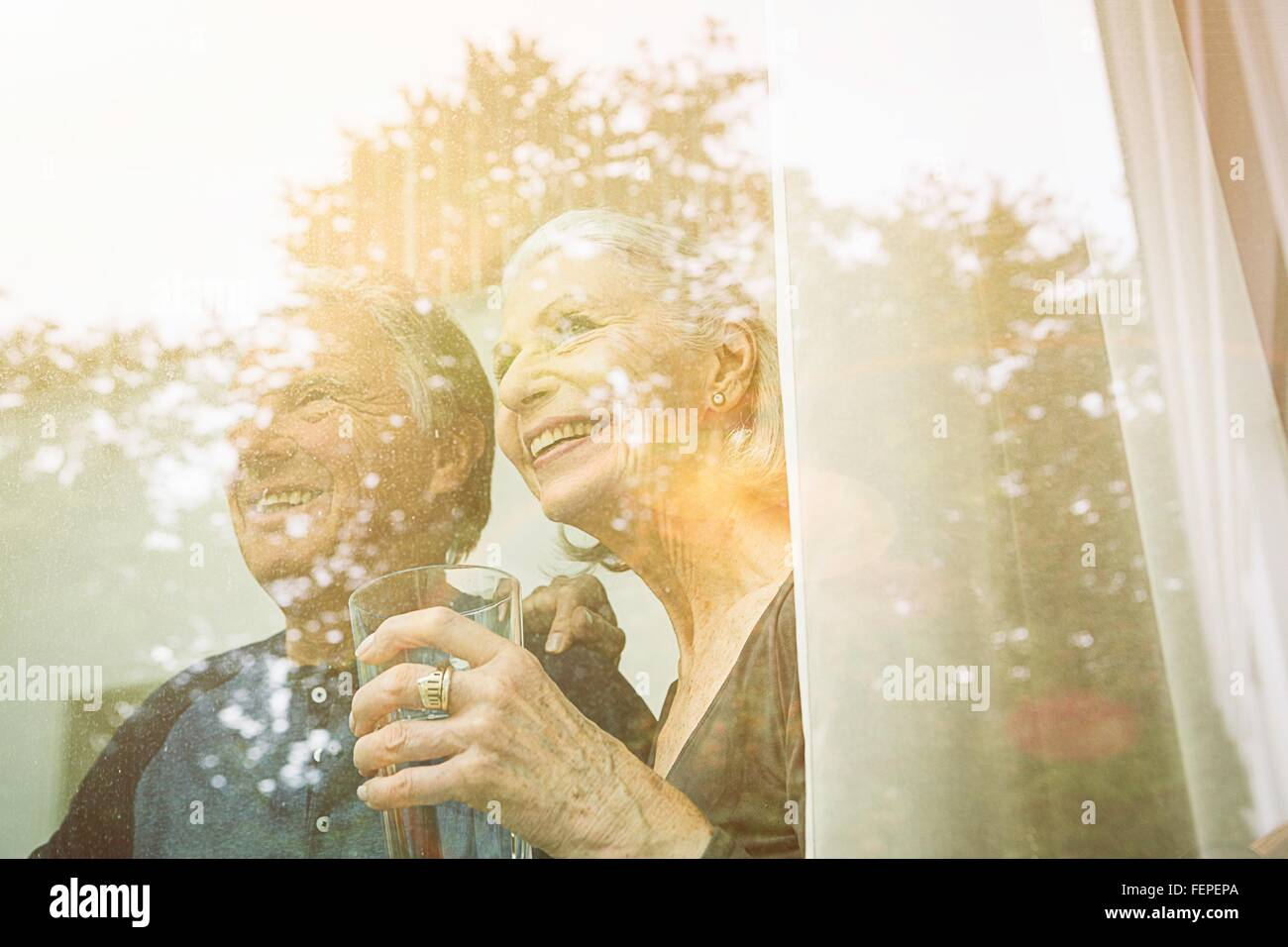View through window of senior couple holding tumbler looking away smiling - Stock Image