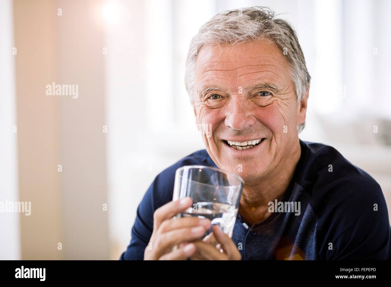 Portrait of senior man holding tumbler of water looking at camera smiling - Stock Image