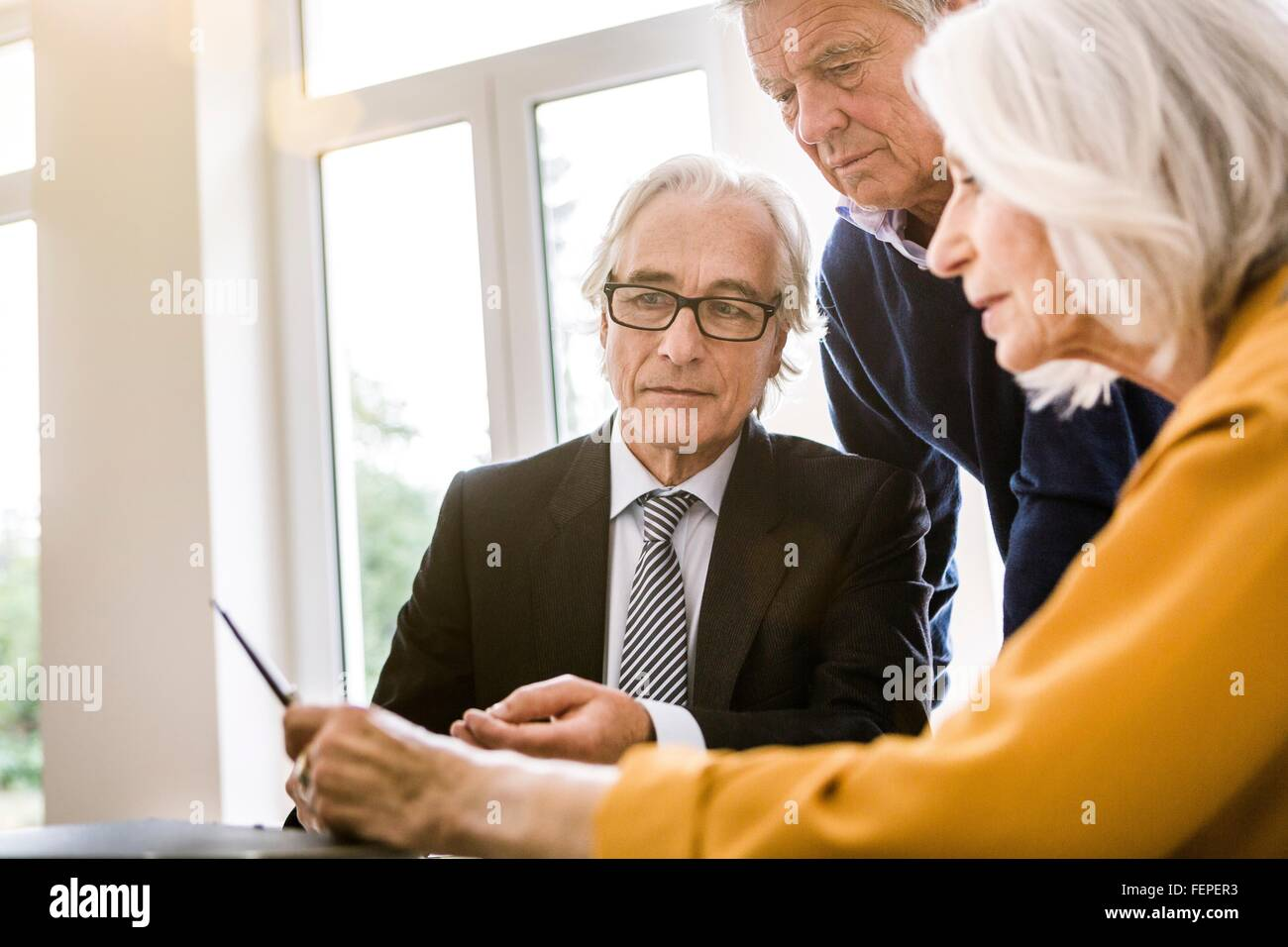 Senior adults in business meeting discussing paperwork - Stock Image