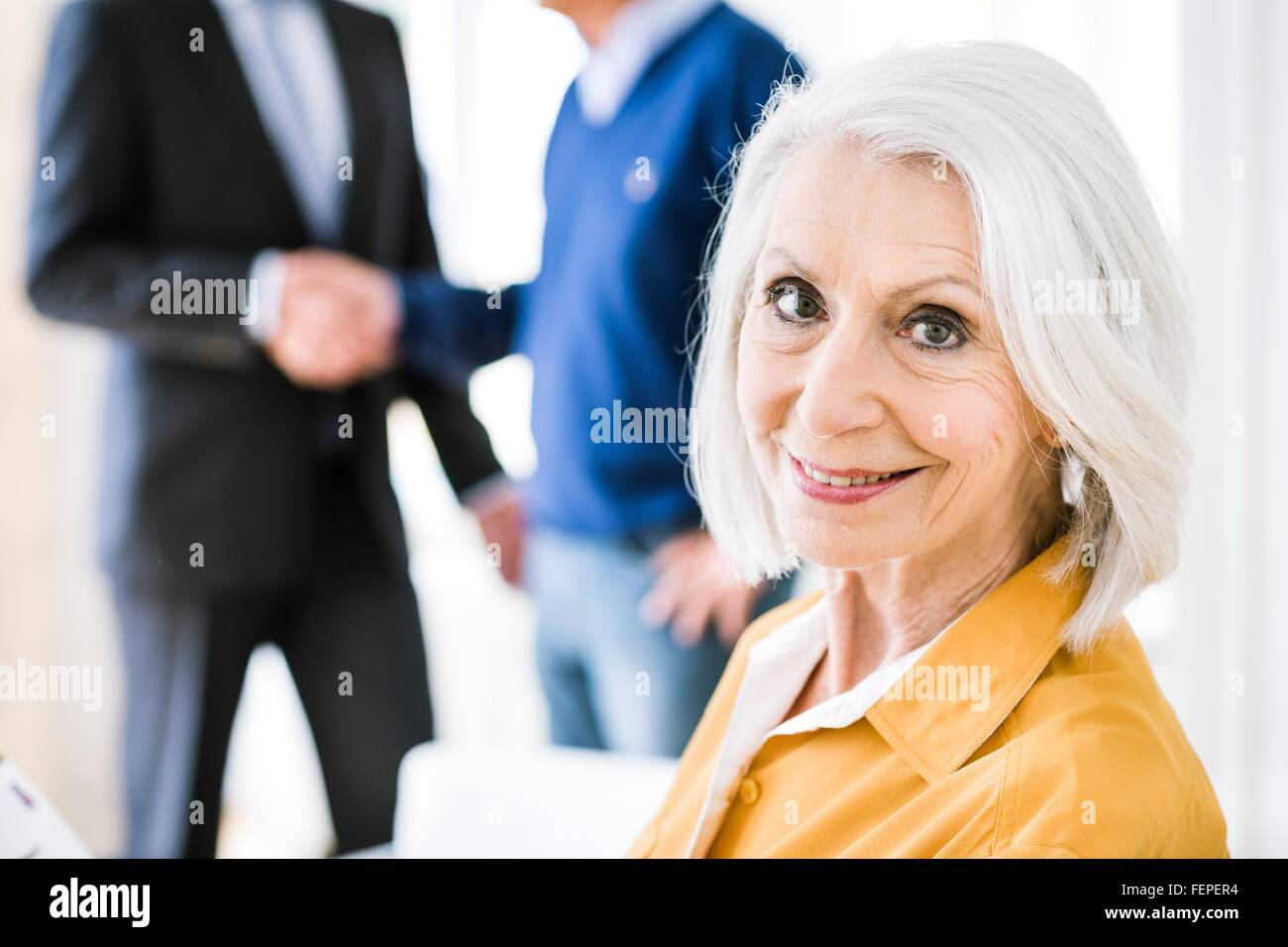 Senior woman in business meeting looking over shoulder at camera smiling - Stock Image