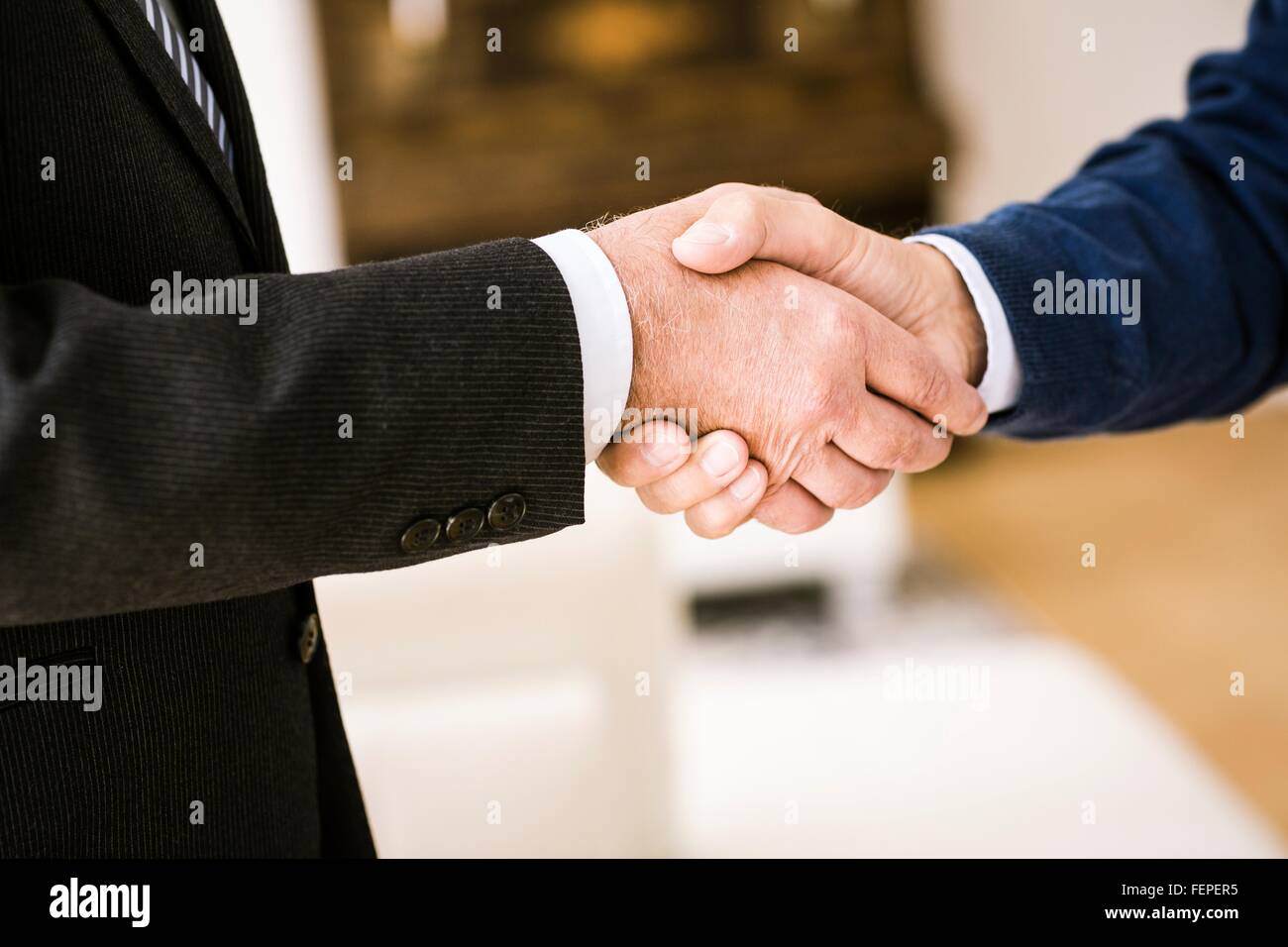 Cropped view of senior men shaking hands - Stock Image
