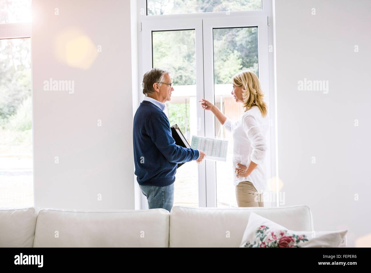 Couple in front of french doors discussing paperwork - Stock Image