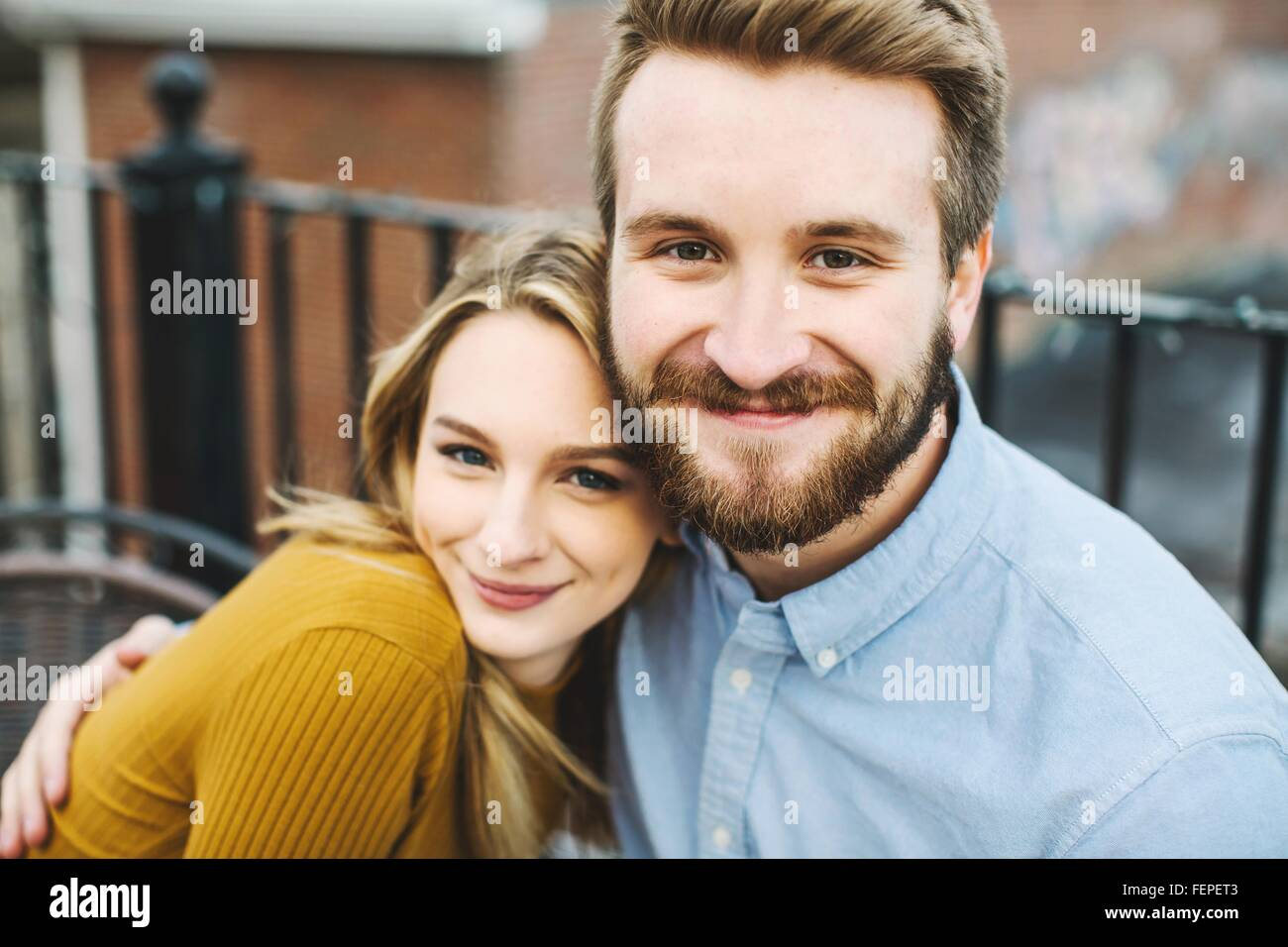 Portrait of romantic young couple on city rooftop terrace - Stock Image