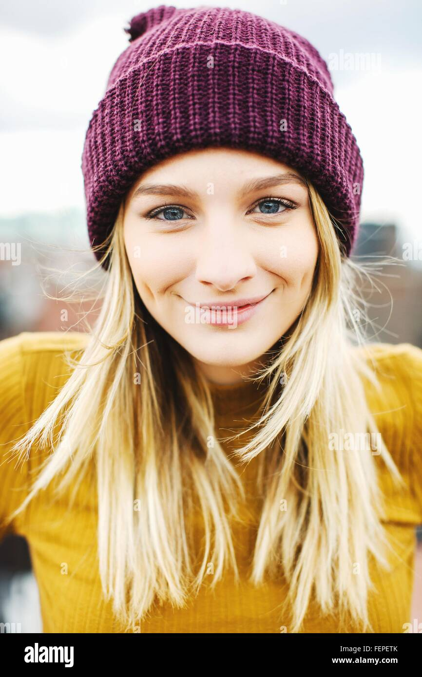 Portrait of young woman wearing knitted hat - Stock Image