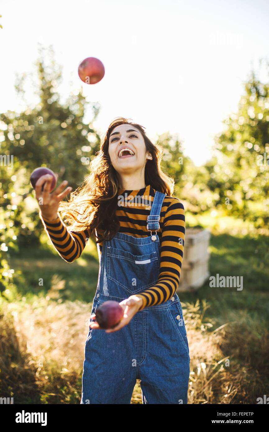 Young woman, in rural environment, juggling with apples - Stock Image