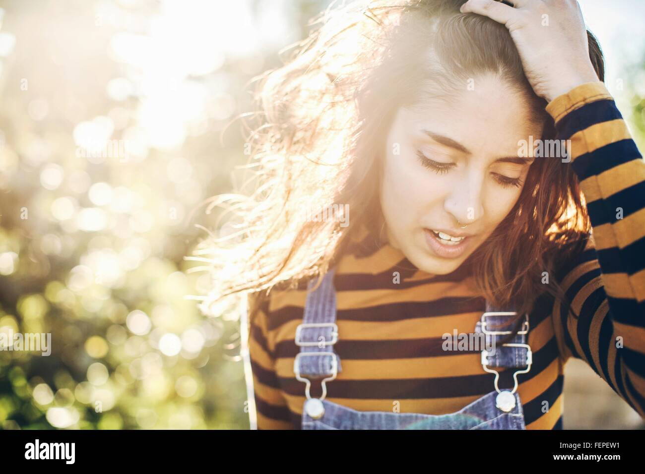 Young woman in rural environment, running fingers through hair - Stock Image