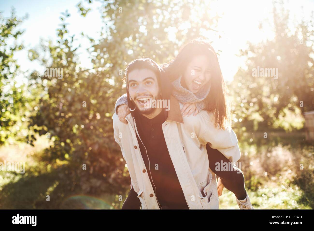 Young man giving young woman piggyback ride, outdoors - Stock Image