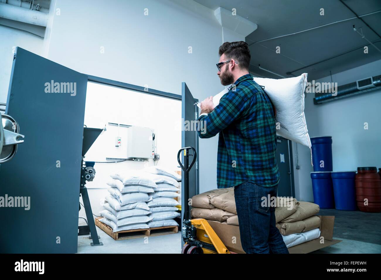 Side view of young man in warehouse carrying gunny sack on shoulder - Stock Image