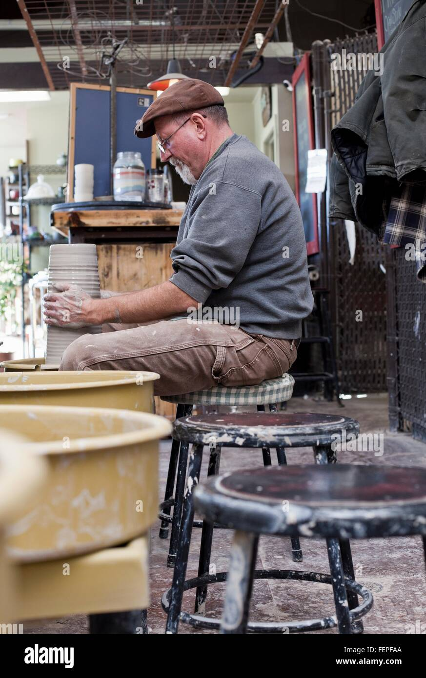 Side view of potter in workshop sitting at pottery wheel shaping clay pot - Stock Image