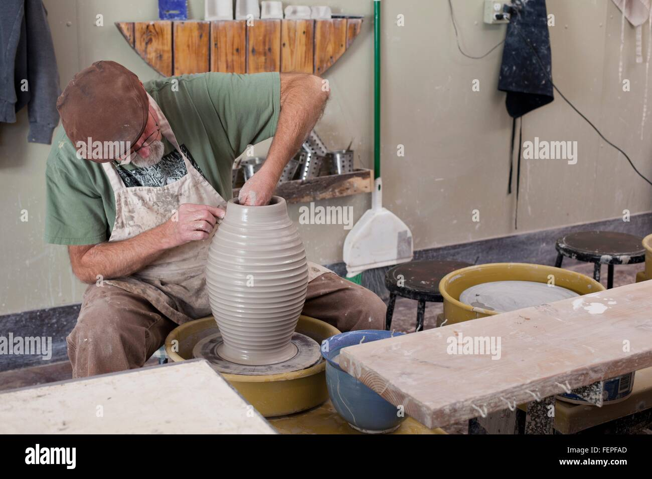 Potter wearing flat cap sitting at pottery wheel shaping clay vase - Stock Image