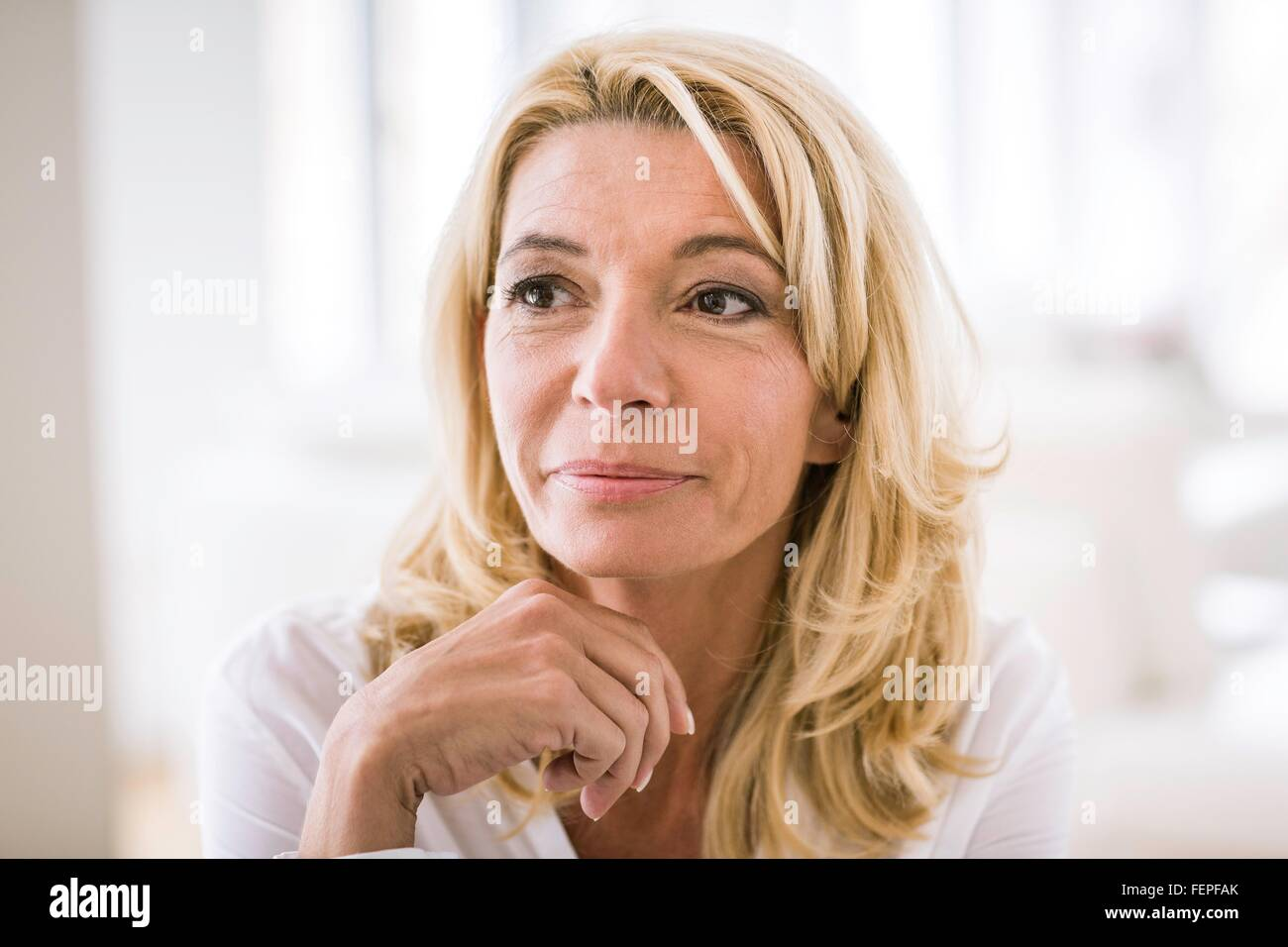 Portrait of blonde haired woman looking away - Stock Image