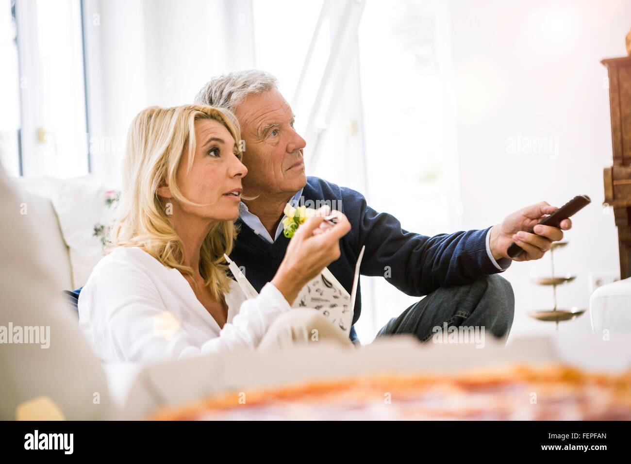 Side view of couple sitting on sofa eating salad watching television - Stock Image