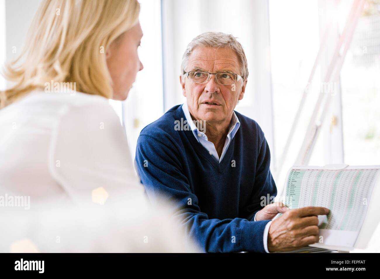 Couple sitting discussing paperwork - Stock Image
