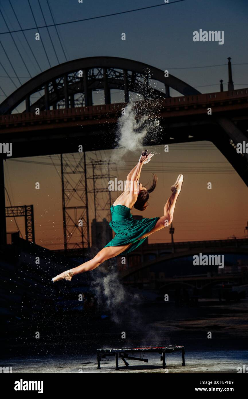 Female dancer leaping whilst releasing powder explosion at sunset, Los Angeles, USA - Stock Image