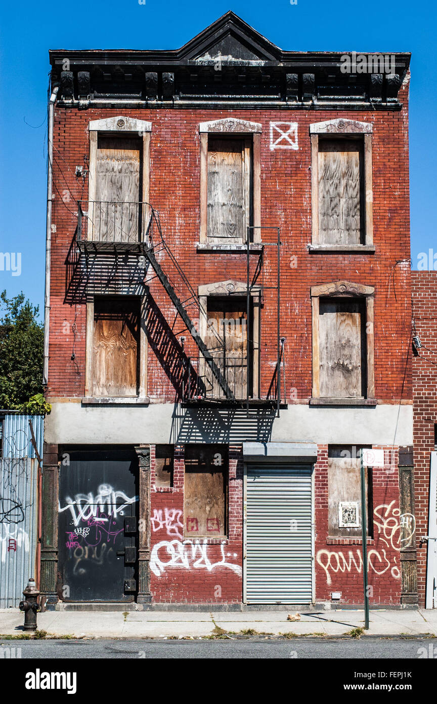 Decrepit old house with red bricks and graffiti in Queens (New York) - Stock Image