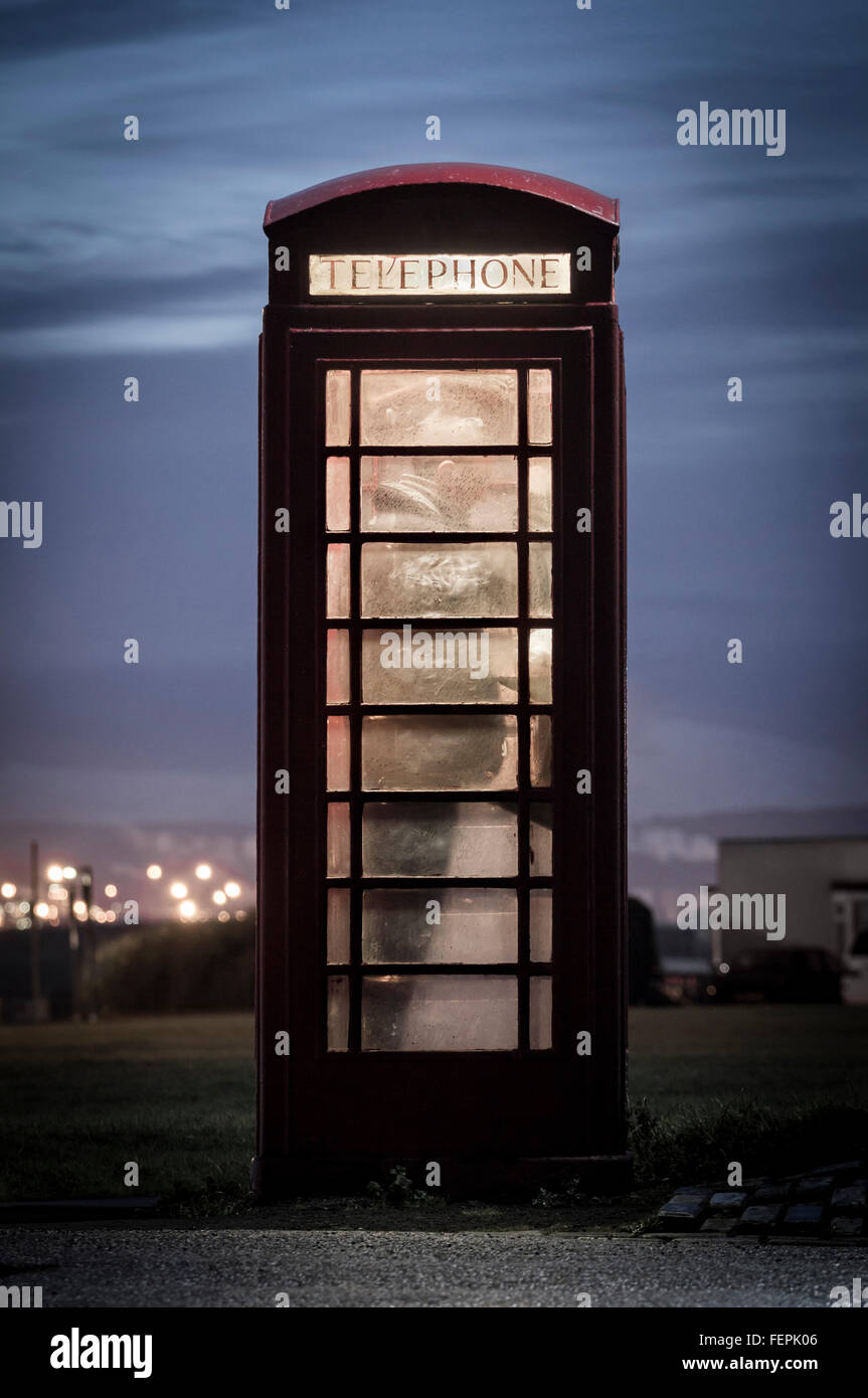 Man making call from red telephone box at night. UK - Stock Image