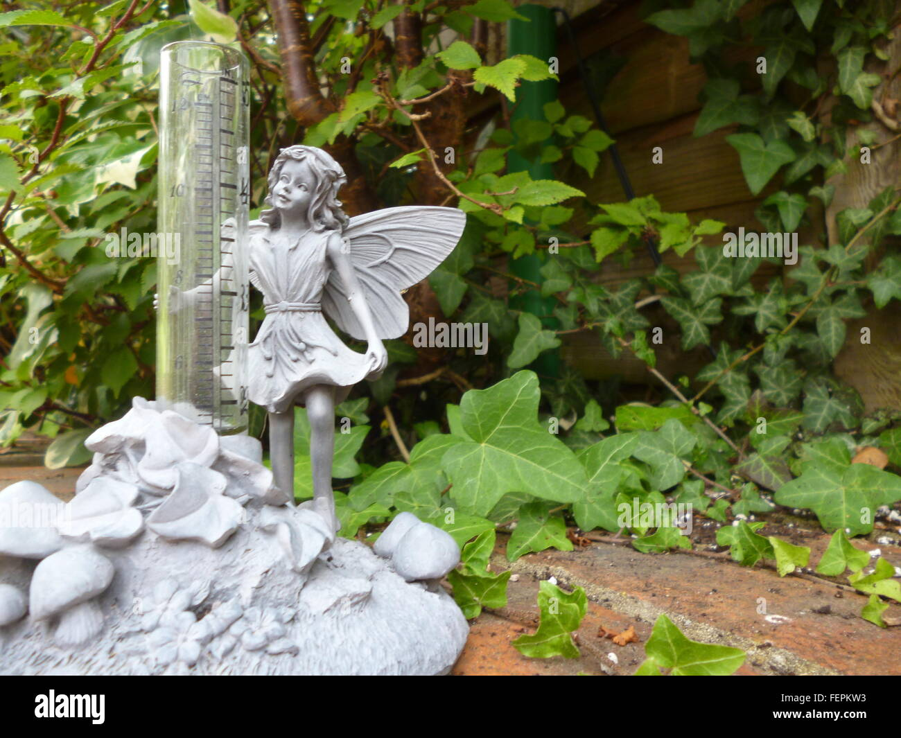 Garden Thermometer With Angel Statue Against Plants   Stock Image