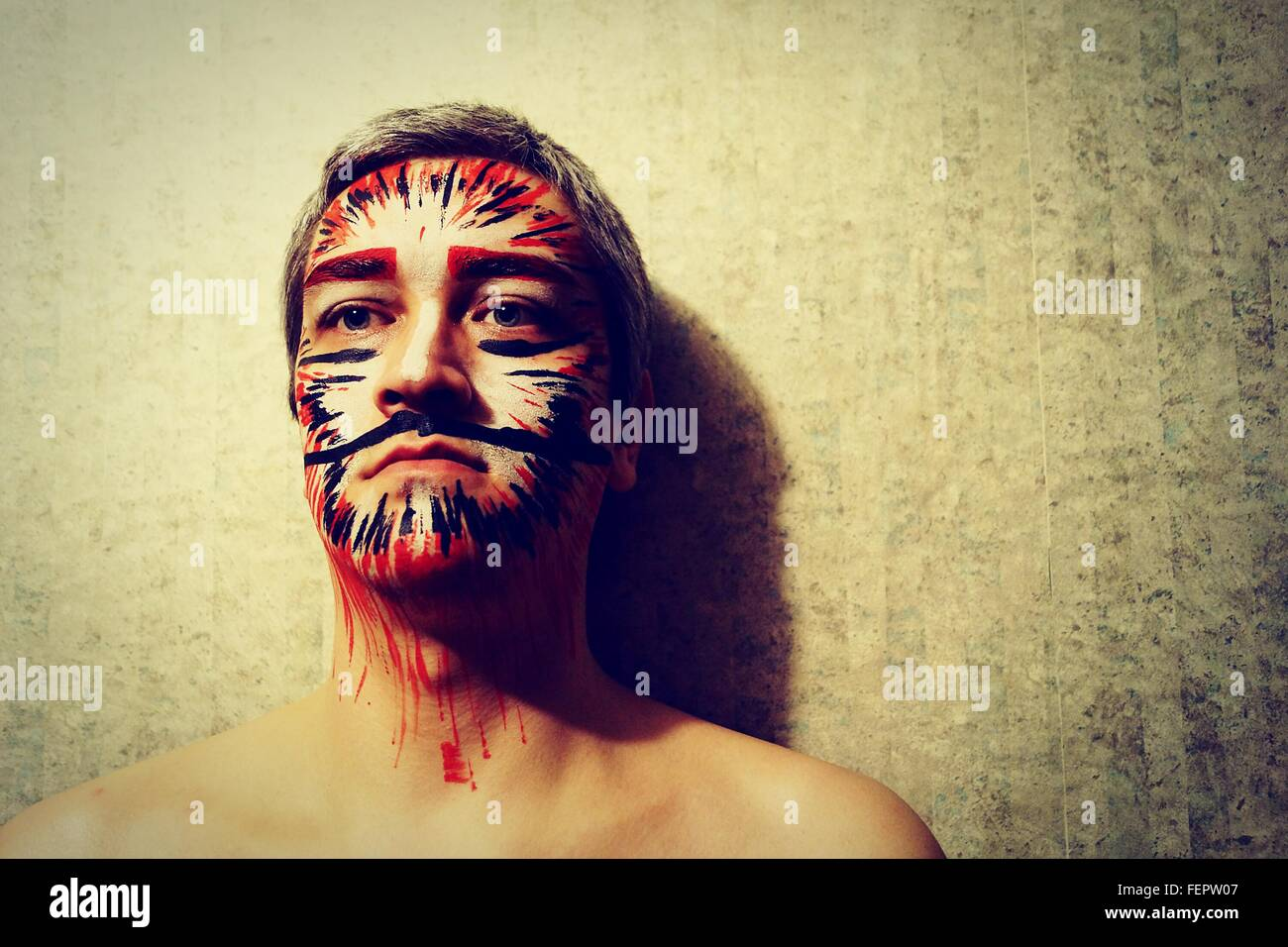 Close-Up Of Shirtless Man In Face Paint Against Wall - Stock Image