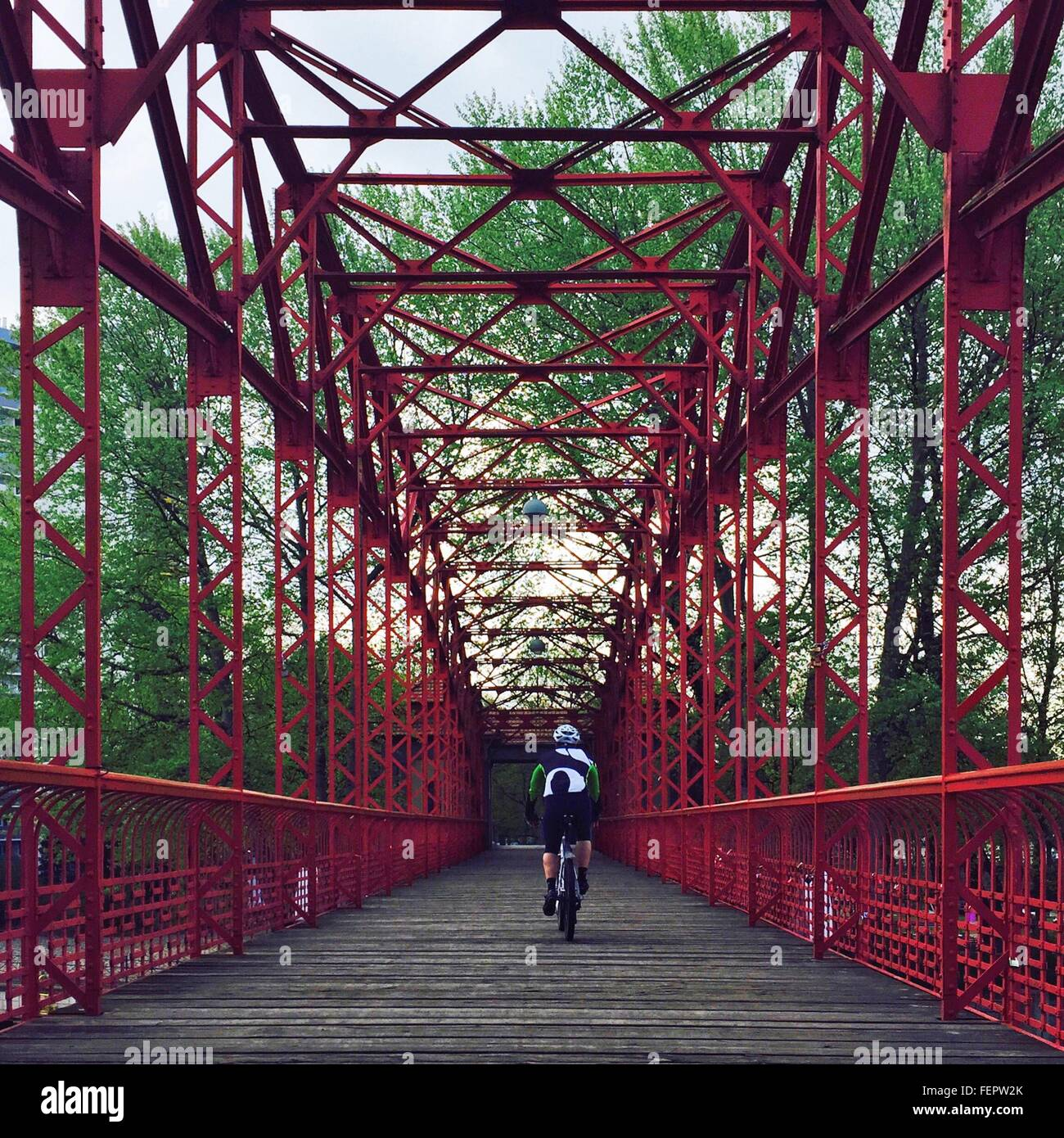 Rear View Of A Man Bicycling On Bridge - Stock Image