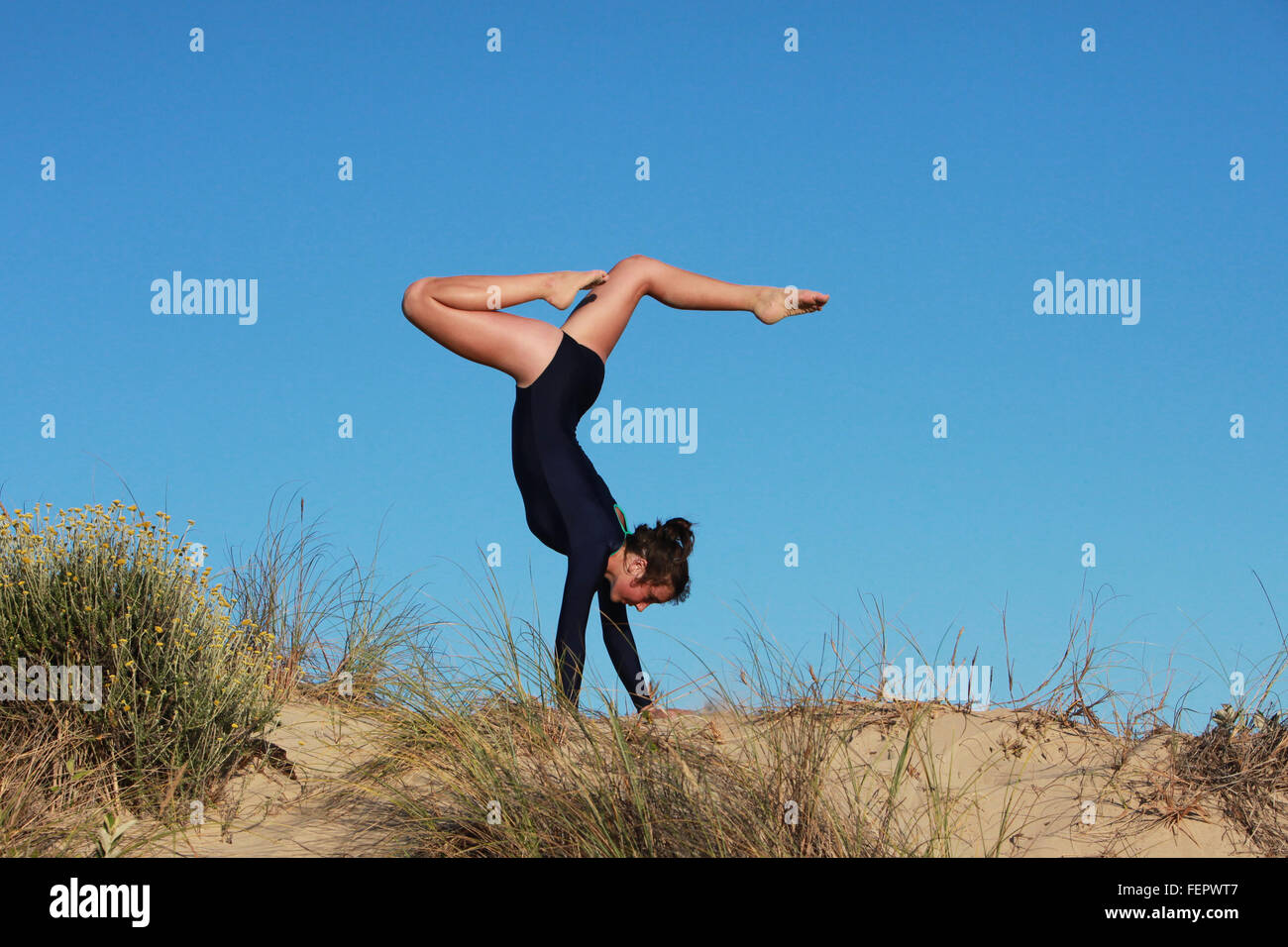 A gymnast is doing her routine on the beach in South Africa. - Stock Image