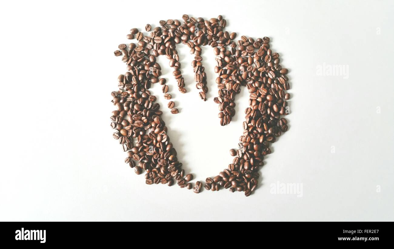 High Angle View Of Hand Made In Coffee Bean Heap On White Background - Stock Image