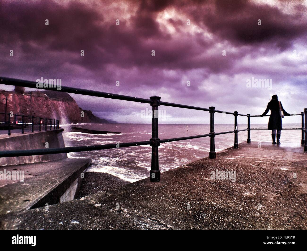 Rare View Of Woman Standing On Observation Point At Jurassic Coast - Stock Image