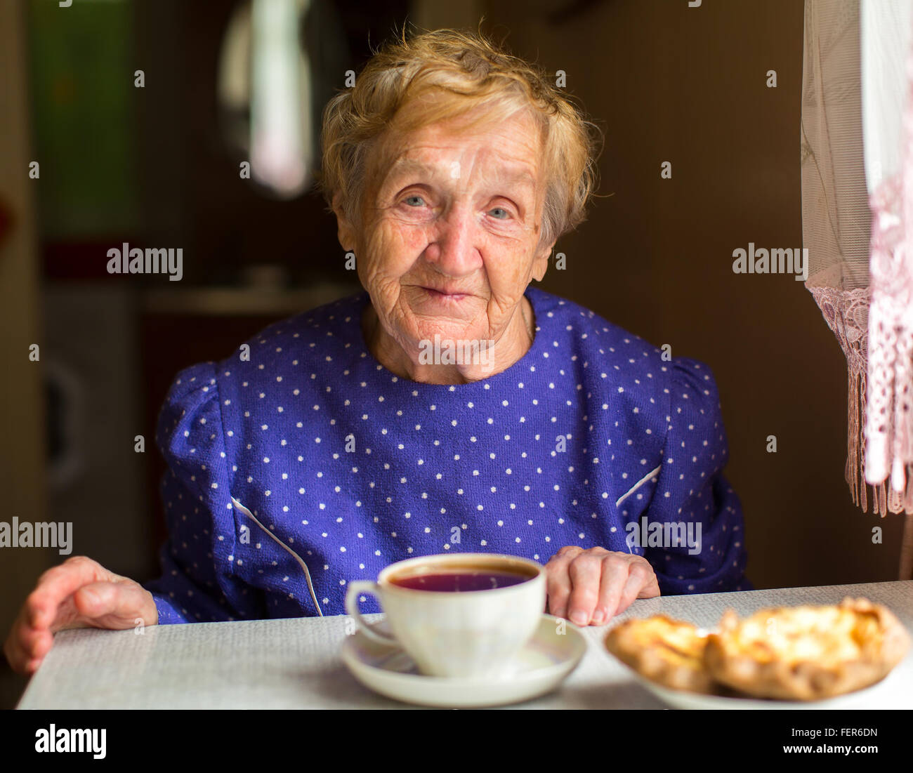 An elderly woman sitting at the table and drinking tea. - Stock Image