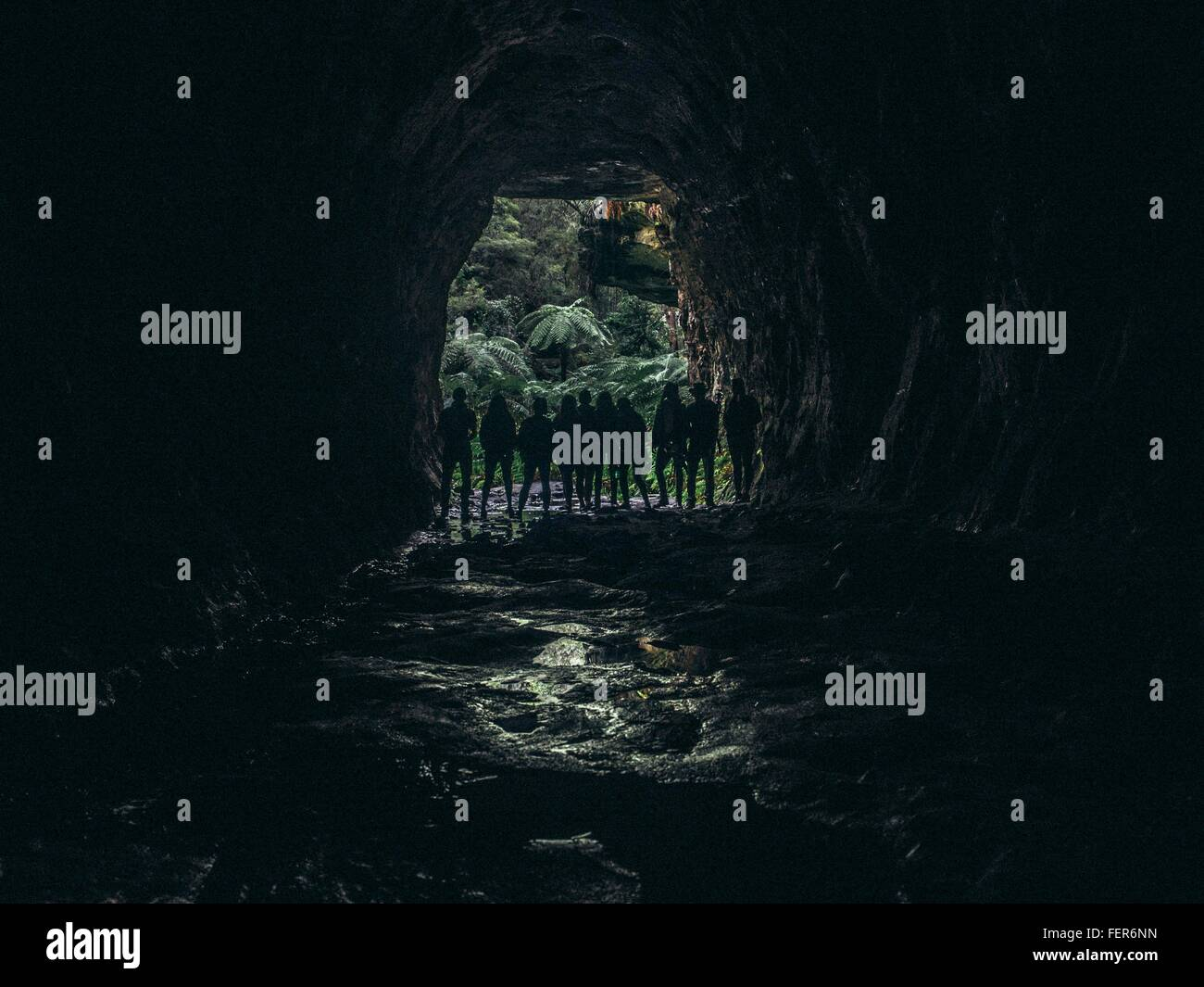 Silhouette Of People Standing At Entrance Of Cave - Stock Image