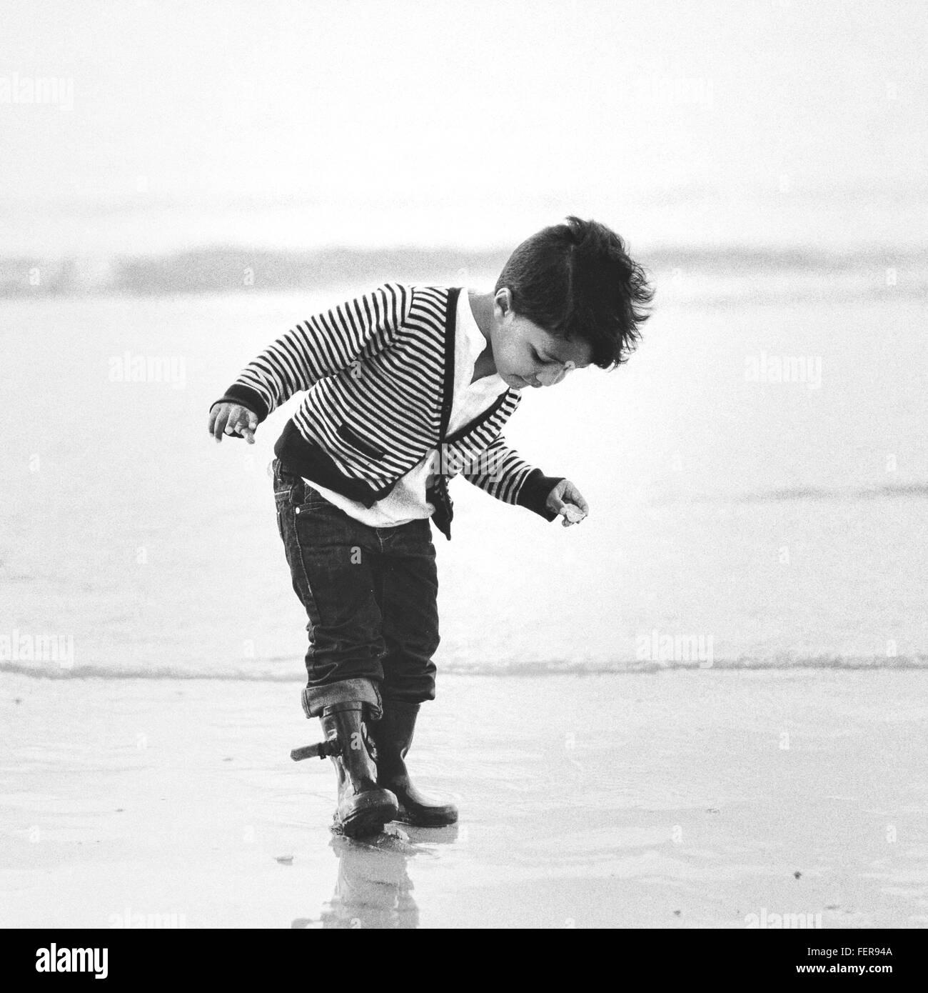 Full Length Of Boy On Shore At Beach - Stock Image
